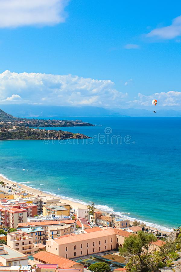 El vuelo del ala flexible sobre la bahía azul hermosa en italiano Cefalu, Sicilia capturó en una imagen vertical El Paragliding e imagen de archivo libre de regalías