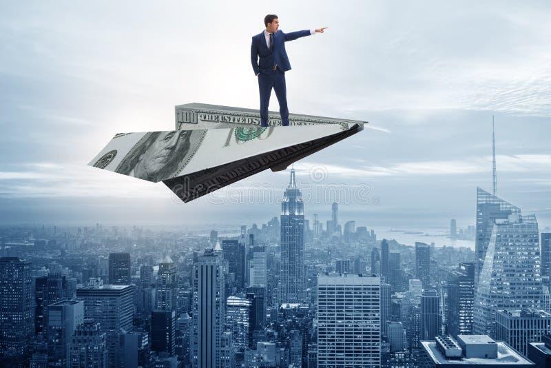 El vuelo del hombre de negocios en el avión de papel en concepto del negocio foto de archivo libre de regalías