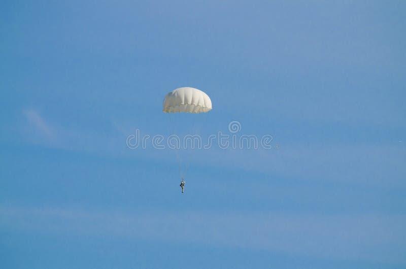 El vuelo del paracaidista en un cielo azul foto de archivo