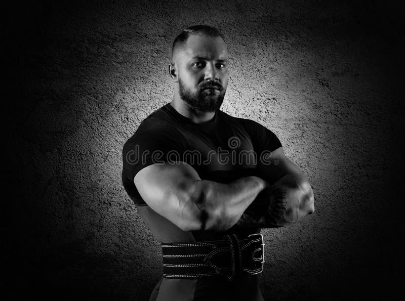 El weightlifter se coloca en una actitud amenazadora con el brazo enorme cruzado fotografía de archivo