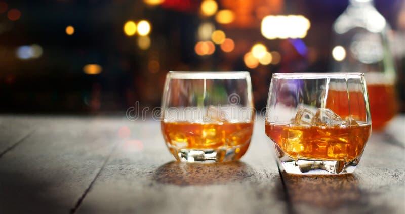 El whisky bebe con hielo en la tabla de madera en el backgrou de las luces de la noche fotos de archivo