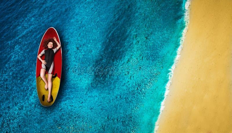 El windsurfer de sexo femenino en wetsuit miente a bordo fotos de archivo
