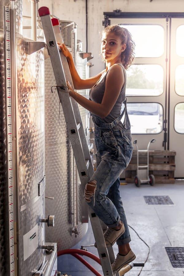 El winemaker femenino controla la calidad del vino foto de archivo