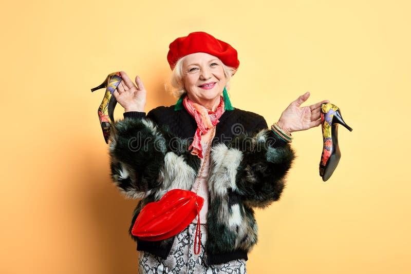 El womna elegante del encanto en el casquillo rojo, abrigo de pieles ha comprado nuevos zapatos fotografía de archivo libre de regalías