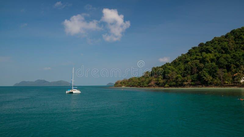 El yate blanco cerca a la isla tropical y a una playa foto de archivo libre de regalías