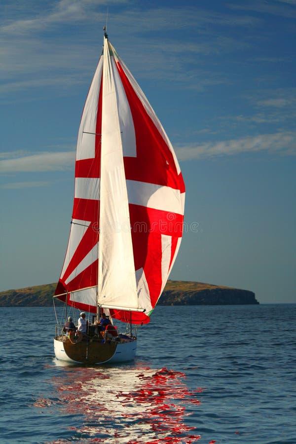 El yate con una vela roja cerca de la isla. 2 fotos de archivo