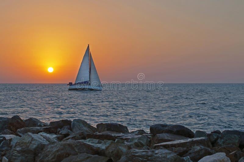 El yate en el fondo de la puesta del sol fotografía de archivo libre de regalías
