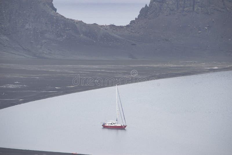 El yate náutico se encuentra en el anclaje de la Antártida, con la península antártica como telón de fondo imagen de archivo