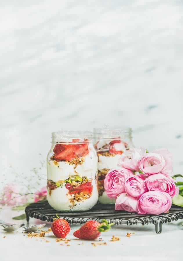 El yogur griego, granola, desayuno fresco en tarros, raninkulus de la fresa florece imagen de archivo