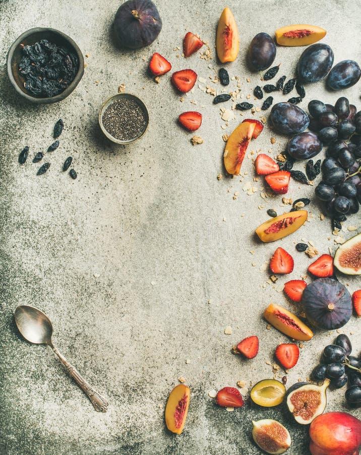 El yogur griego, la fruta fresca y las semillas del chia ruedan, composición vertical imagen de archivo