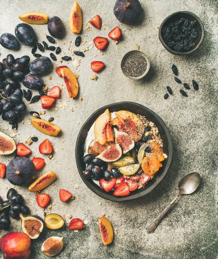 El yogur griego, la fruta fresca y las semillas del chia ruedan, fondo concreto imágenes de archivo libres de regalías