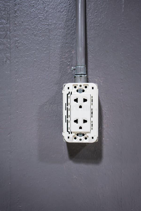 El zócalo plástico blanco del enchufe conectó con el tubo del metal plateado en VE imagen de archivo