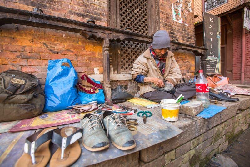 El zapatero trabaja en la calle El sistema de castas es hoy todavía intacto pero las reglas no son tan rígidas como eran en el pa foto de archivo libre de regalías