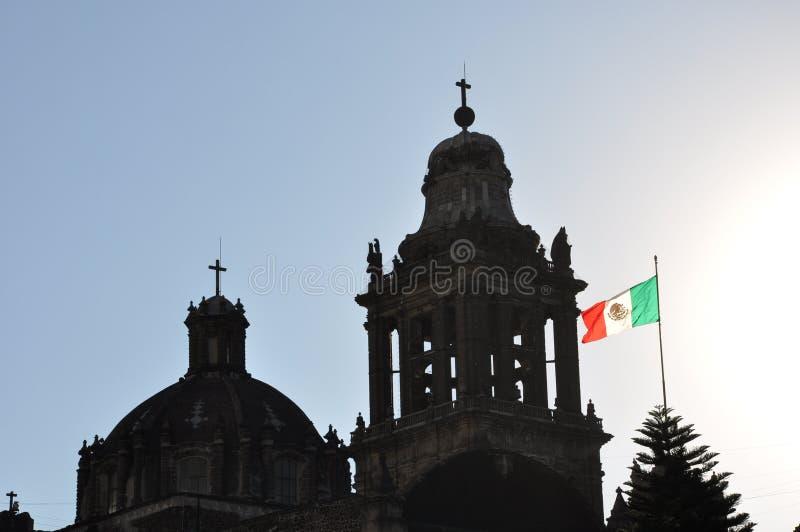 El Zocalo, Cuidad de Mexico. Mexican flag blowing in the wind on top of a silhouette of the basilica in El Zocalo, Mexico City stock image