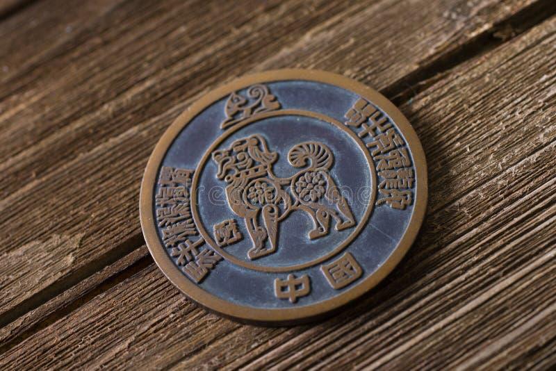 El zodiaco animal del perro firma adentro una moneda en la madera fotos de archivo libres de regalías