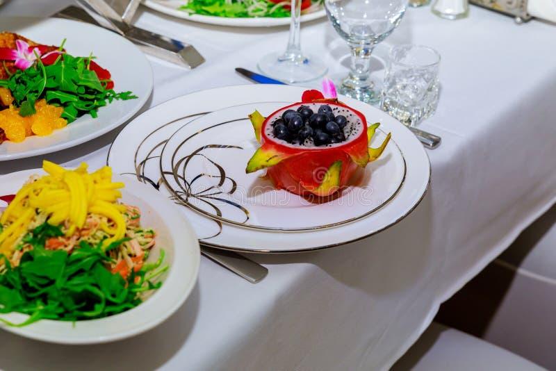 El zumo de fruta rojo del dragón en una paja del plato, adornada con Plumeria florece sobre tela florida fotografía de archivo