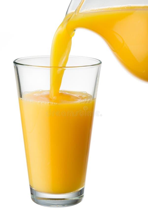 El zumo de naranja se vierte de la jarra en el vidrio imagen de archivo libre de regalías