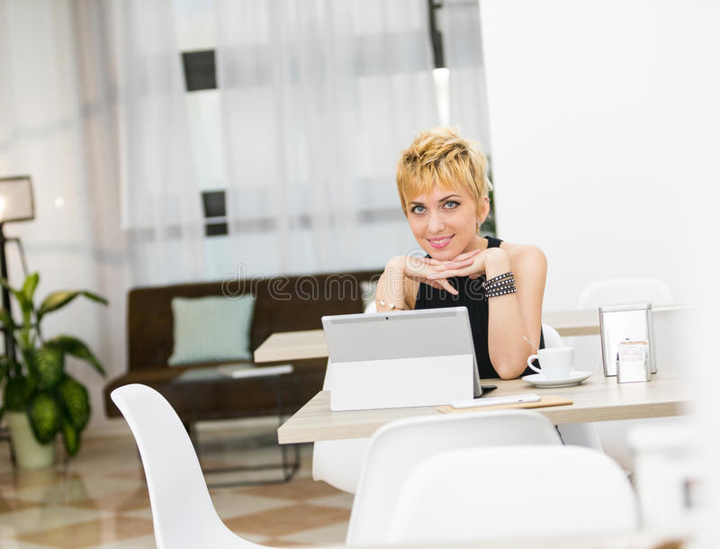 Elaboración de la mujer de negocios del hogar en una cafetería fotos de archivo libres de regalías
