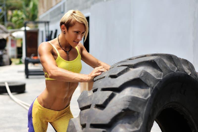 Elaboración femenina del atleta con un neumático enorme, torneado y flippin foto de archivo libre de regalías