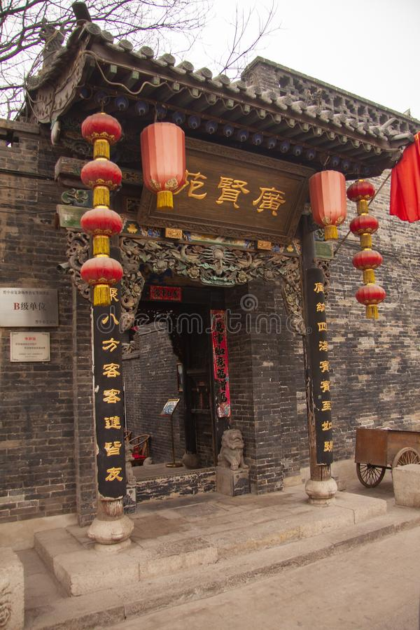 Elaborate entrance to an ancient Chinese house with sculptures, red lanterns, writings in gold and a red flag. Beijing, China stock image