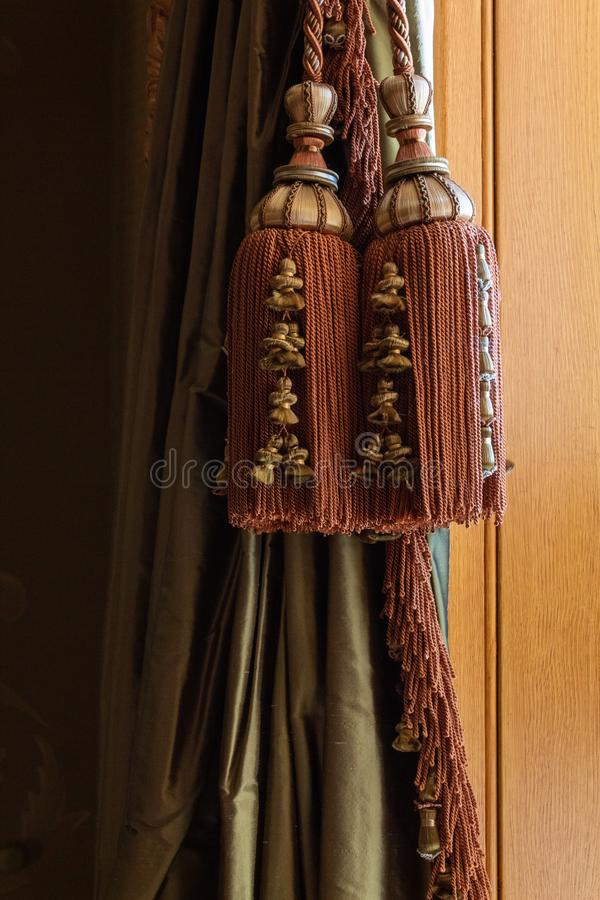 Elaborate large window curtain tie back tassels, cords, and trim over green silk curtains, warm wood background. Vertical aspect stock photo