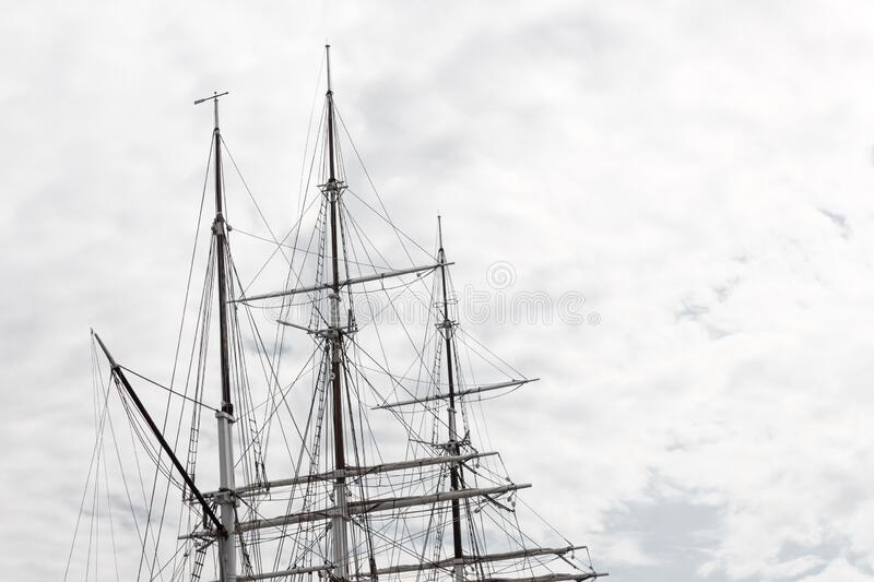 Elaborate rigging on a three mast tall ship against a gray sky. Horizontal aspect royalty free stock image