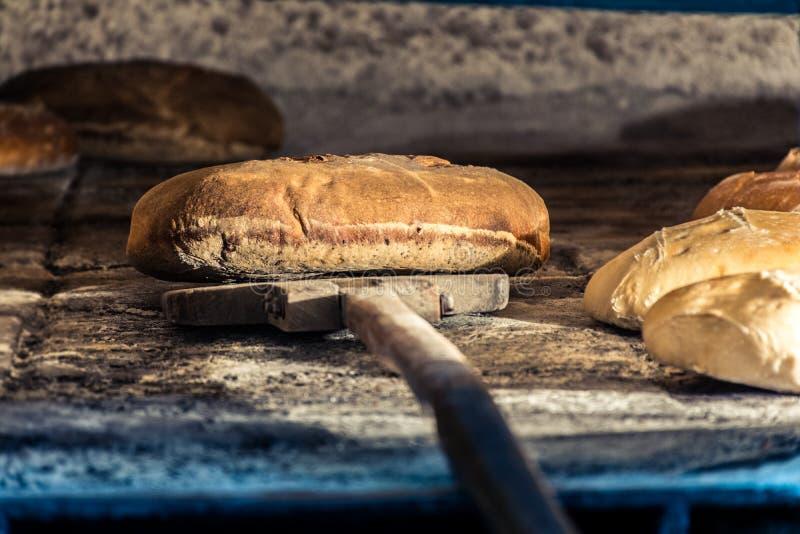 Elaborazione di pane in forno di legno tradizionale fotografia stock