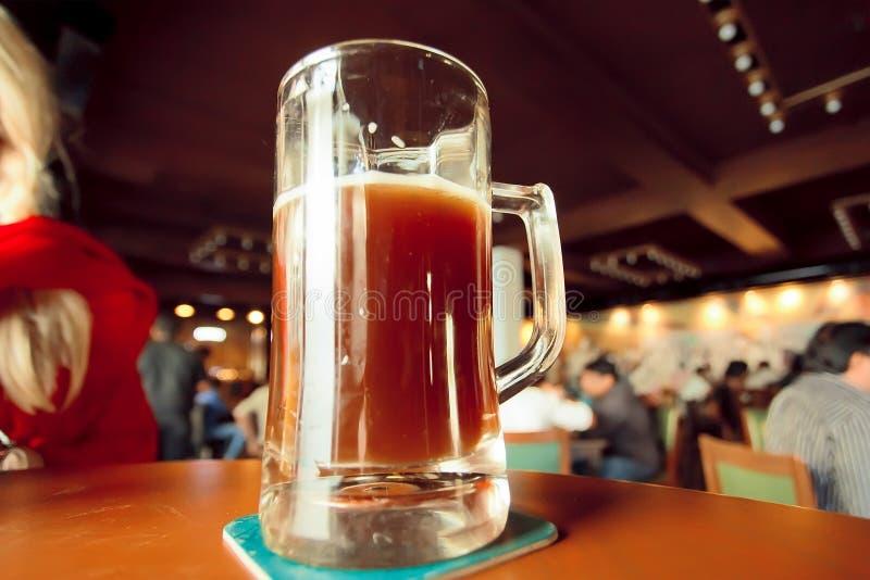 Elabori la tazza di birra sulla tavola della barra di spazio enorme con i bevitori ed i mangiatori immagini stock libere da diritti