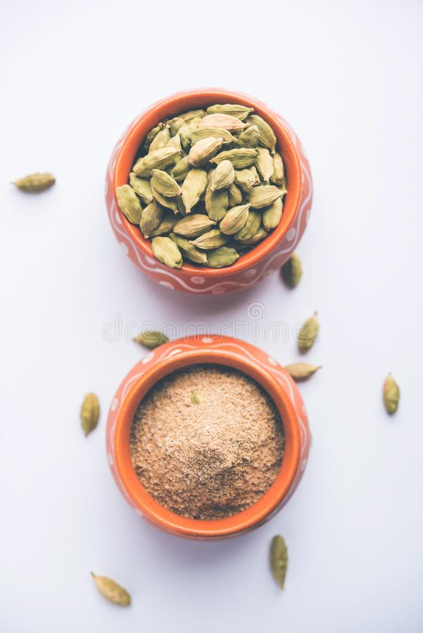 Cardamom powder or elaichi powder in bowl over moody background with pods. royalty free stock images
