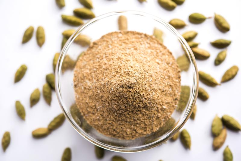 Cardamom powder or elaichi powder in bowl over moody background with pods. royalty free stock photo