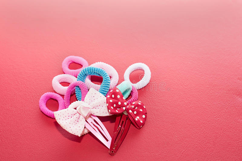Elastic bands and buckles. Hair accessories such as elastic bands and buckles in the form of bows. Red background royalty free stock photo