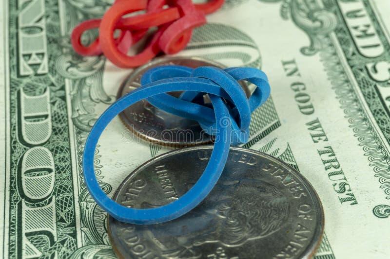 Elastici e monete torti sulle banconote in dollari fotografie stock