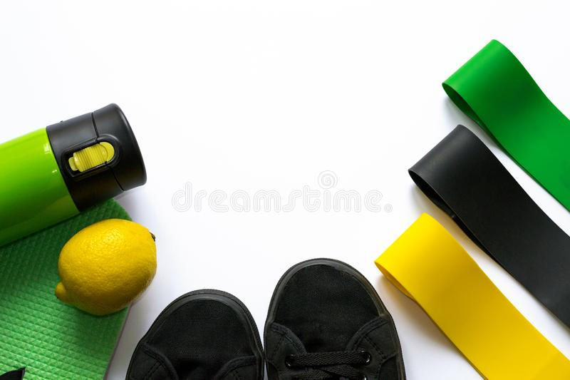 Elastische Eignungsgummiexpander von gelben, grünen und schwarzen Farben auf weißem Hintergrund mit copyspace Thermosflascheflasc stockfoto