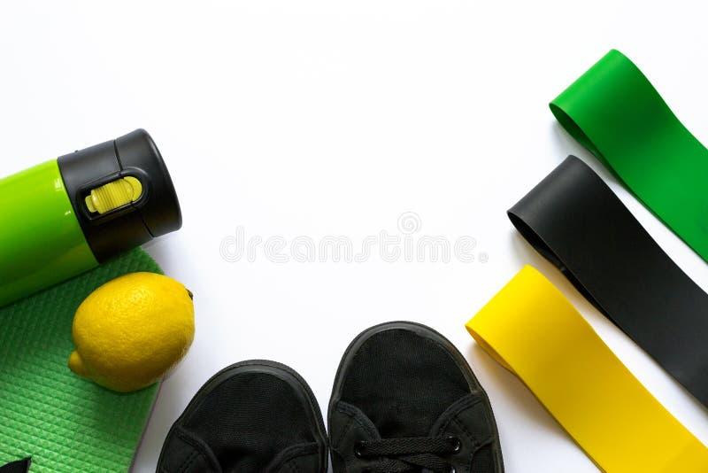 Elastiska konditiongummiexpanders av gula, gröna och svarta färger på vit bakgrund med copyspace Termosflaska, citron, arkivfoto