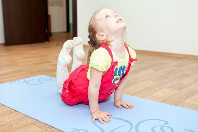 Elastyczna dziewczyna robi exerciseson na macie obraz stock