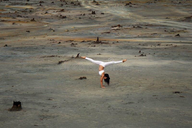 Elastyczna gimnastyczki dziewczyna w pięknej pozie na tle apokaliptyczny krajobraz w pustyni zdjęcia stock