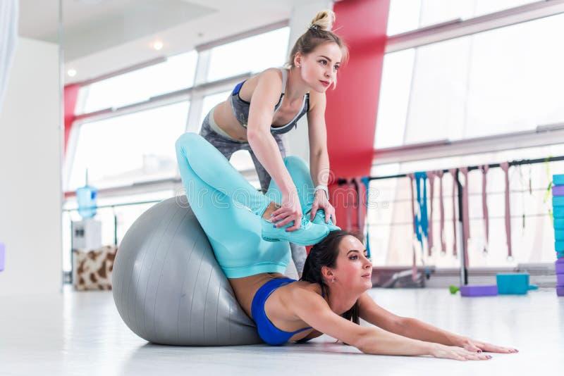 Elastyczna kobieta robi postępowemu rozciągania ćwiczeniu Ładny żeński instruktor pomaga szczupłej brunetki dziewczyny robi joga  zdjęcie stock