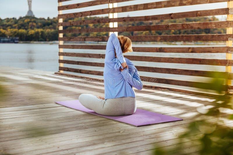 Elastyczna kobieta rozciąga tylnych mięśnie podczas gdy robić joga zdjęcia royalty free