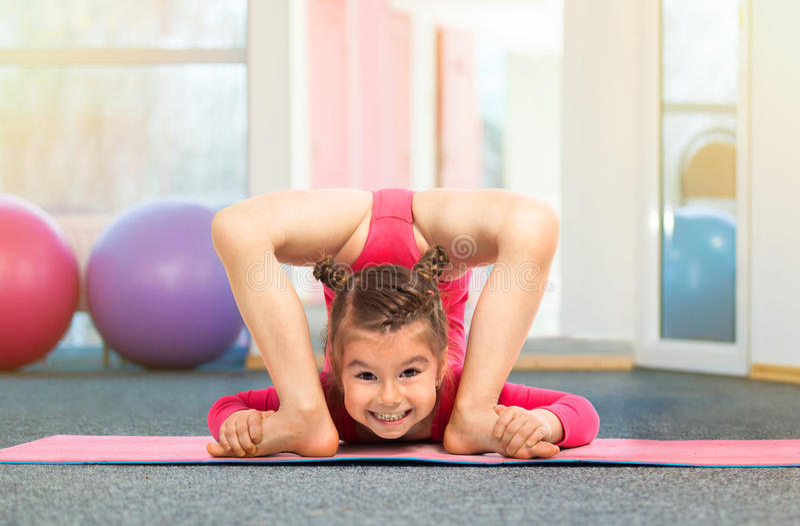 Elastyczna małej dziewczynki gimnastyczka robi akrobatycznemu ćwiczeniu w gym obraz stock
