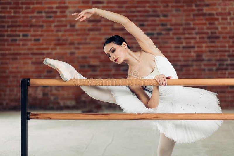 Elastyczna piękna kobieta robi baletniczej pozie przed barre zdjęcia stock