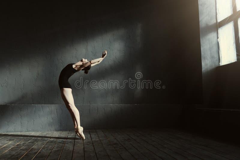 Elastyczny baletniczego tancerza rozciąganie w zmroku zaświecał studio zdjęcie royalty free