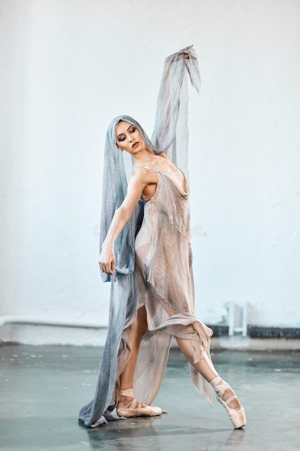 Elastyczny baletniczego tancerza rozci?ganie w zmroku za?wieca? studio zdjęcie stock