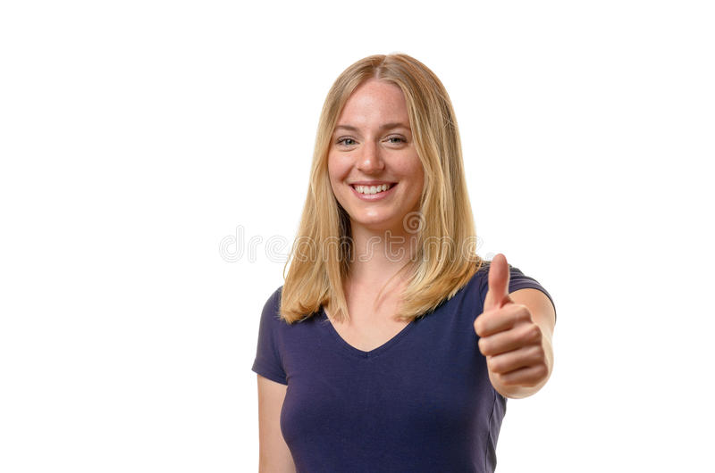 Elated young woman giving a thumbs up. Elated attractive young blond woman giving a thumbs up gesture of approval, success and agreement, upper body isolated on stock image