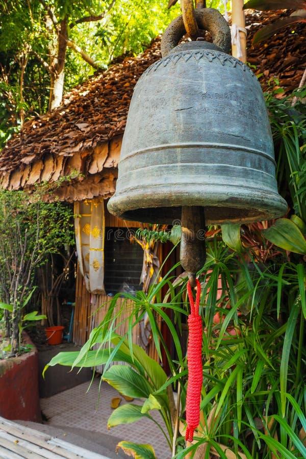 Żelazny dzwon z lokalnym bambusa domem obraz royalty free