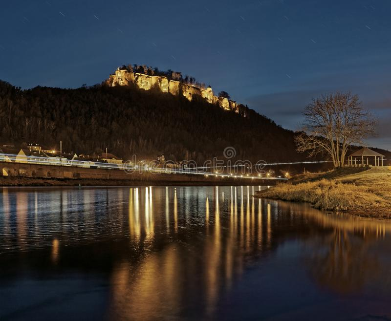 Elbe Sandstone Mountains - Night view to the fortress `Königstein`. Elbe Sandstone Mountains - Night view of the fortress `Königstein` from the banks of royalty free stock image