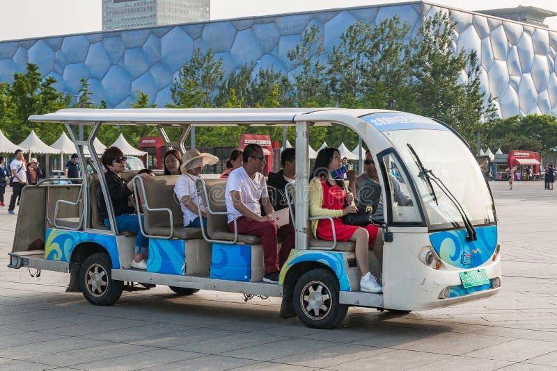 Elbilen med turister i bakgrunden av det nationella simningkomplexet i det olympiskt parkerar av Peking royaltyfria foton