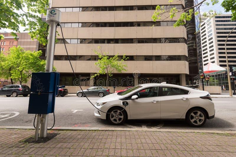 Elbilen pluggade in i en EV-uppladdningsstation royaltyfri bild