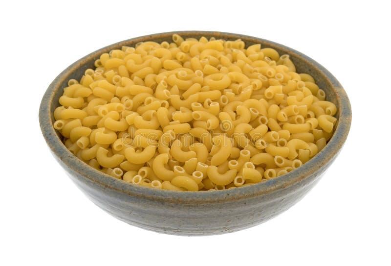 Elbow macaroni in a stoneware bowl. stock photo