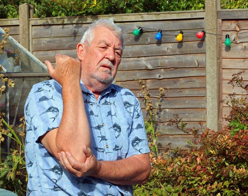 Elbow pain. Arthritis. painful or tennis elbow. Elderly or senior man holding his elbow because of pains. Arthritis or tennis elbow in his joint royalty free stock photo