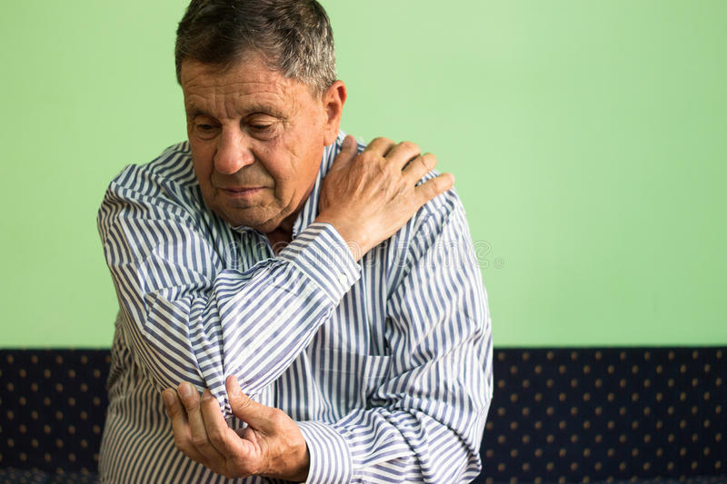 Elbow pain and arthritis. Senior sitting on bed stock images